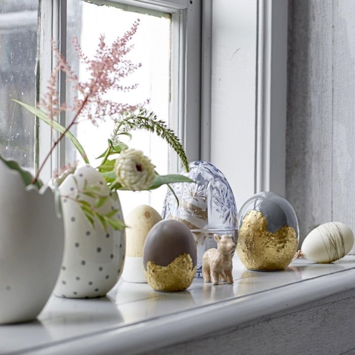 egg shaped vases and figurines placed in front of window with faux flowers easter decoration ideas