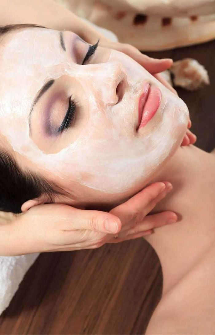 face mask being put on a woman wearing purple eyeshadow hydrating face mask laying down