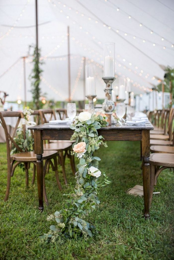 floral table runner on vintage table with vintage chairs around it backyard wedding decorations under white tent