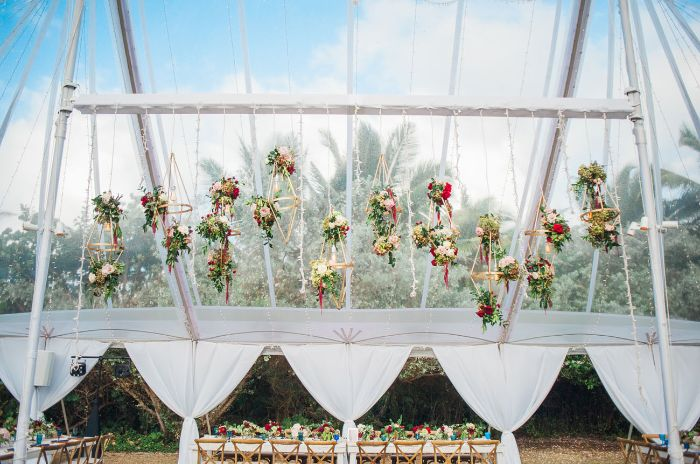 flower bouquets hanging from the ceiling of large tent outside wedding ideas long table under it