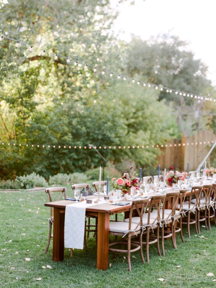 flower bouquets on wood table with lots of chairs strings of lights hanging above it rustic wedding ideas placed on green grass field
