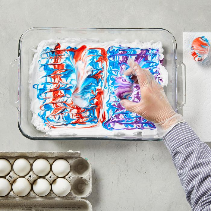 glass tray filled with shaving cream and dye homemade egg dye egg placed in it