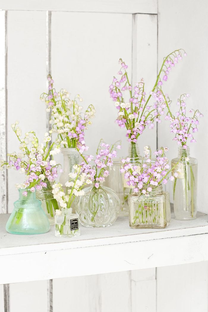 glass vases in different shapes placed on wooden shelf outdoor easter decorations white and purple flowers in them