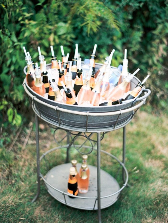 home wedding ideas metal table filled with ice small bottles of moet with straws water bottles