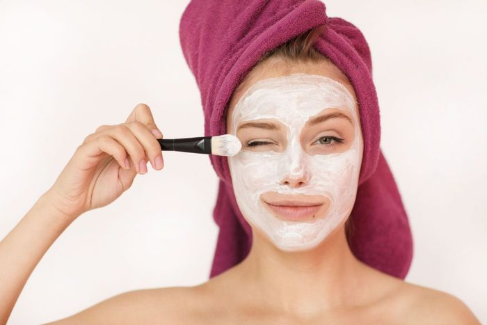 homemade face mask for acne woman wearing purple head towel putting mask on her face with brush