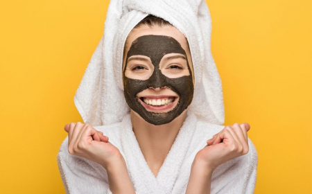 homemade face mask woman wearing face mask white robe and head towel yellow background