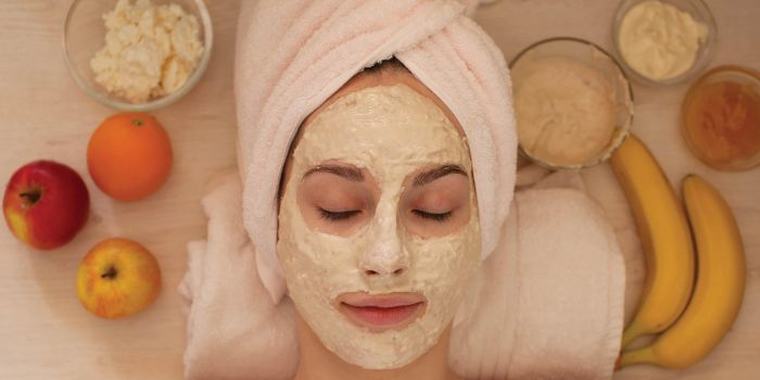 honey face mask woman wearing white towel on her face laying down white face mask on her face