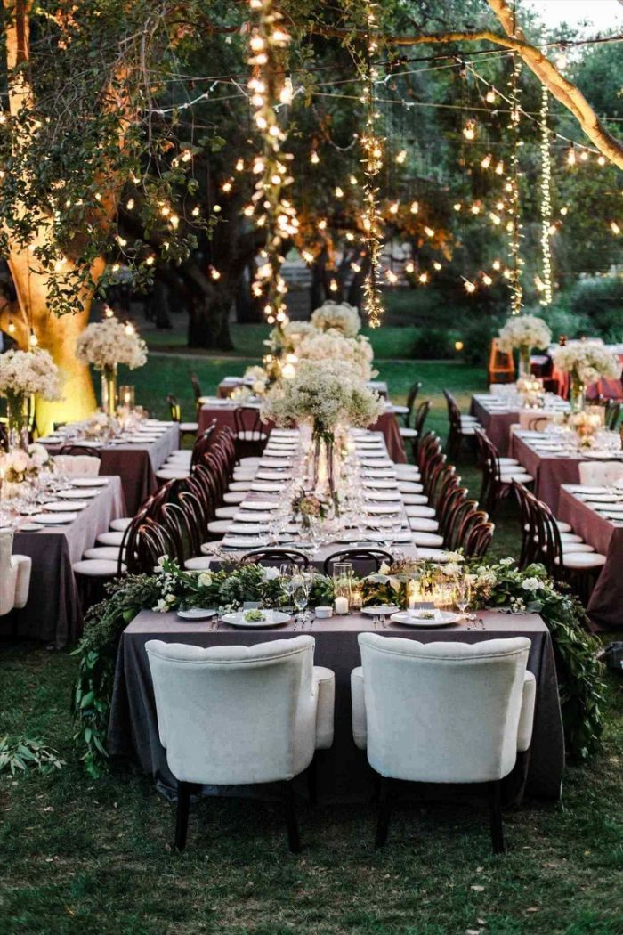 long table with large flower bouquets in the middle backyard wedding decorations strings of lights hanging from trees