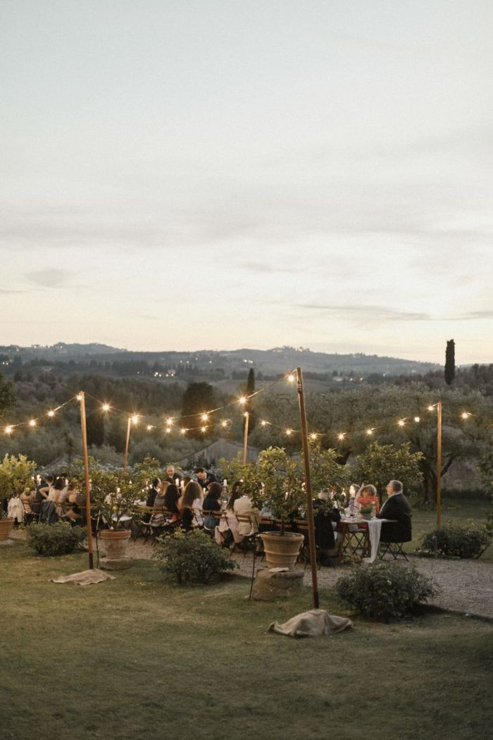 long table with lots of people sitting around it outdoor wedding decorations strings of lights on both sides