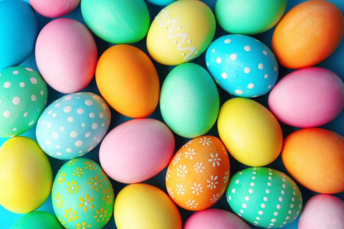 lots of easter eggs placed on blue surface easter egg designs decorated in different colors