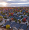 lots of houses photographed from above moving to a new neighborhood fall trees in between at sunrise