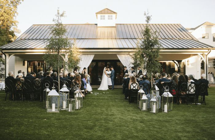 lots of lanterns arranged on both sides of the aisle next to chairs simple wedding decorations bride and groom in the middle