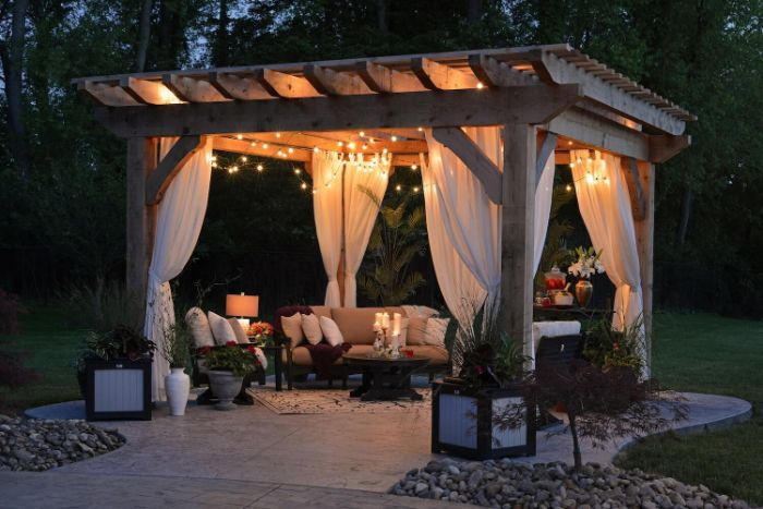 lounge area under a gazebo with white curtains and fairy lights home wedding ideas sofa and armchairs