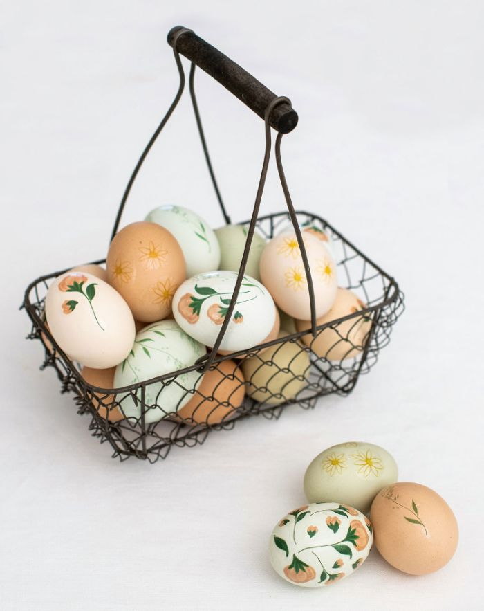 metal basket filled with eggs easter egg coloring different flowers drawn on them