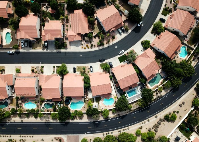 moving to a new neighborhood gated community photographed from above with lots of houses with pools
