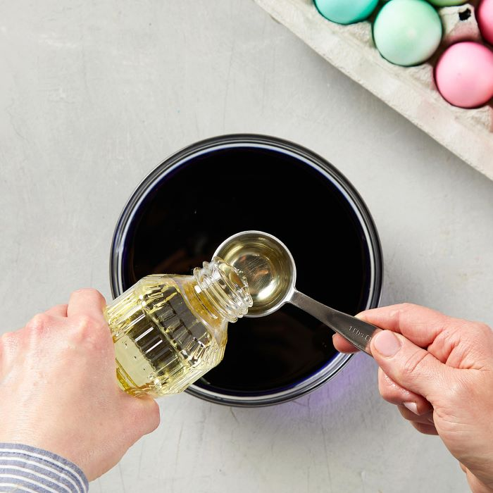 oil being poured into a measuring spoon step by step diy tutorial how to dye eggs with food coloring
