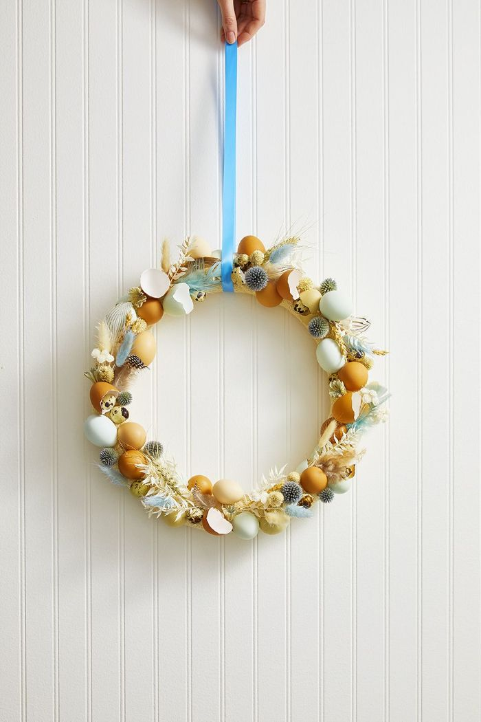 outdoor easter decorations wreath made with eggs and eggshells feathers blue ribbon