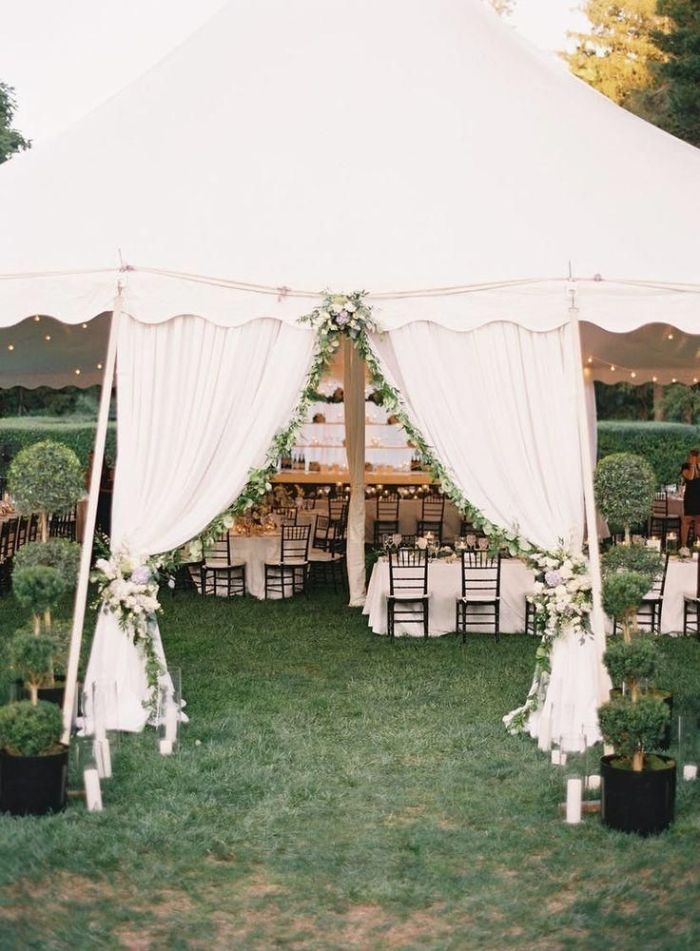 outdoor wedding decorations entrance arch with white curtains and flowers leading to tent with tables under it