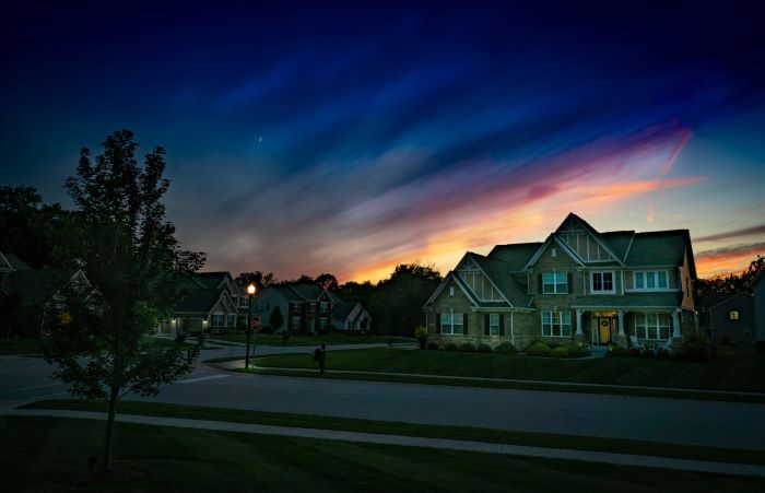 photo of street with large houses on it moving to a new neighborhood dark sky at sunrise