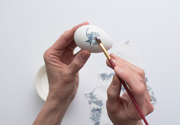 piece of napkin placed on white egg covered with mod podge how to dye eggs