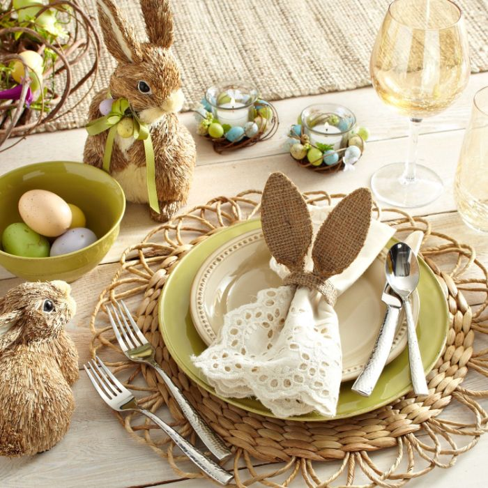 plate setting with white cotton napkin with bunny ears easter decorations small bunny figurines around it