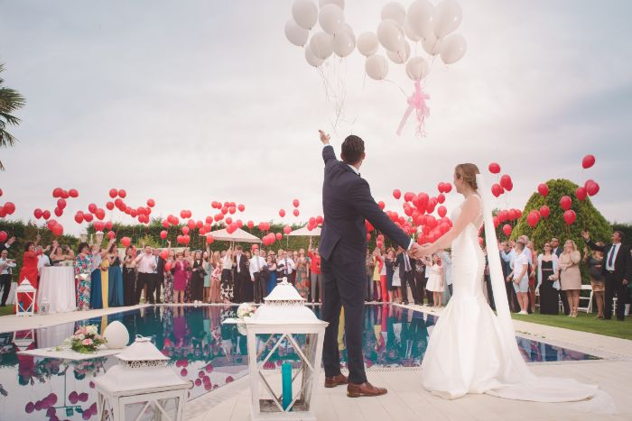 pool wedding home wedding ideas bride and groom standing next to the pool releasing white balloons