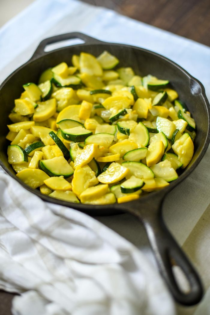 small black skillet filled with summer squash and zucchini pieced summer squash recipes placed on white cloth