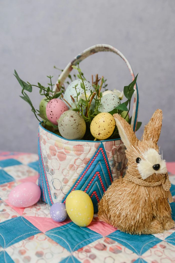 stuffed bunny next to basket made of fabric easter baskets for boys flowers and dyed easter eggs inside