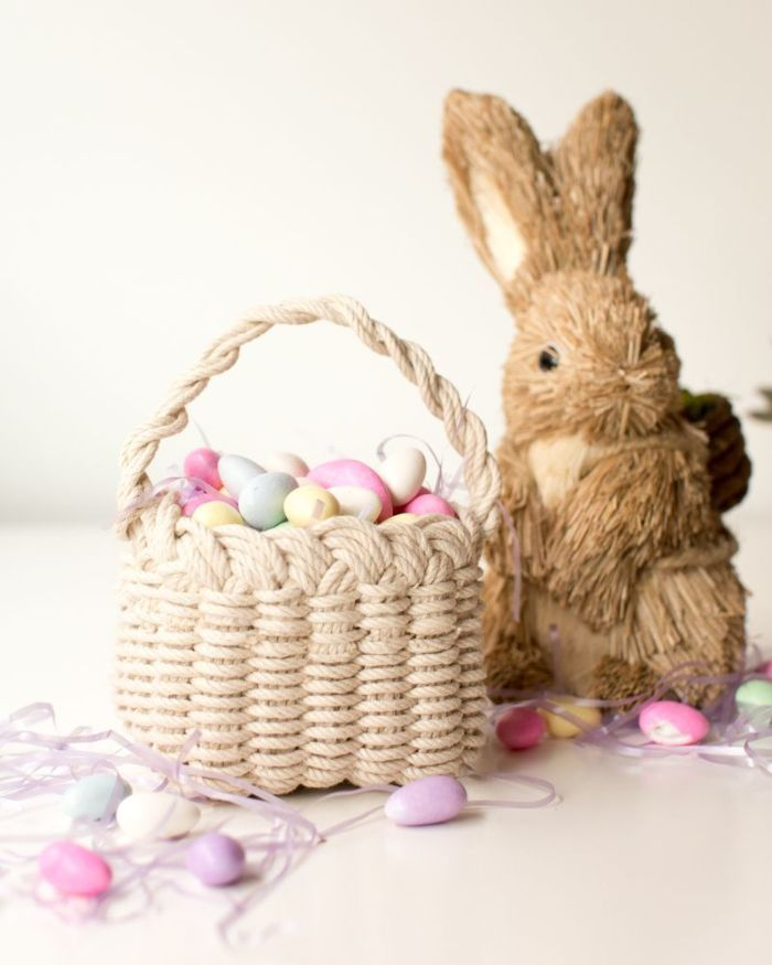 stuffed bunny next to macramé basket adult easter basket filled with egg shaped lights on string