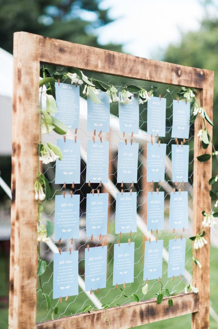 table cards arranged inside wood frame backyard wedding reception decorated with white flowers