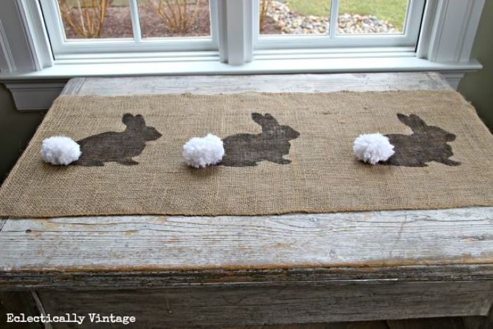 table runner placed on wooden table easter table décor bunny patterns with whtie pom poms for tails
