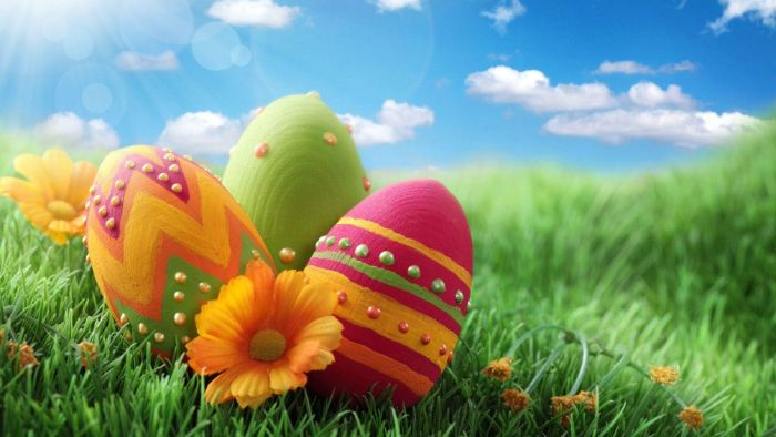 three eggs decorated in green yellow orange and purple easter egg background placed on grass