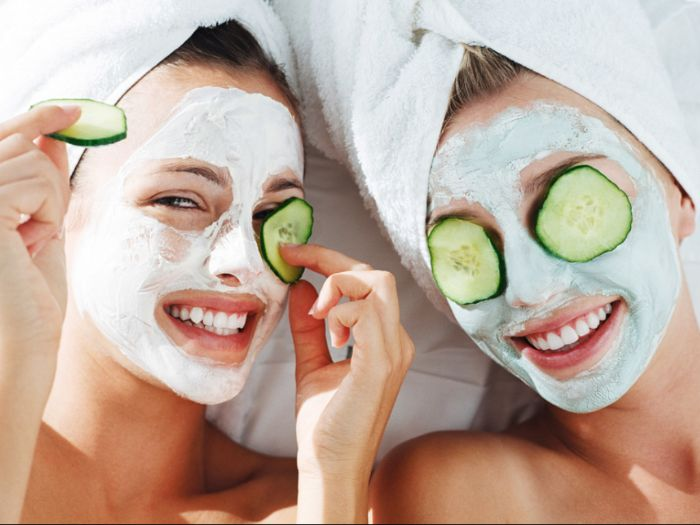 two women wearing white face masks honey face mask two cucumber slices on their eyes