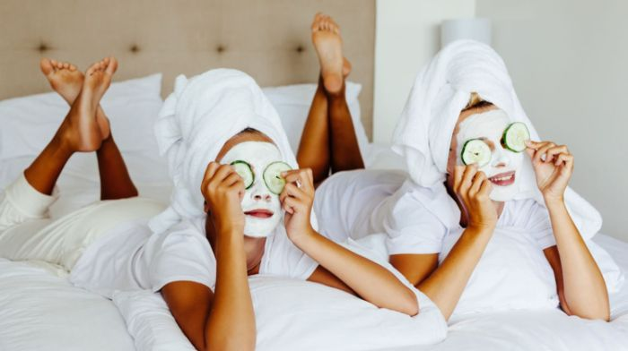 two women wearing white face masks with two cucumber slices on their eyes honey face mask