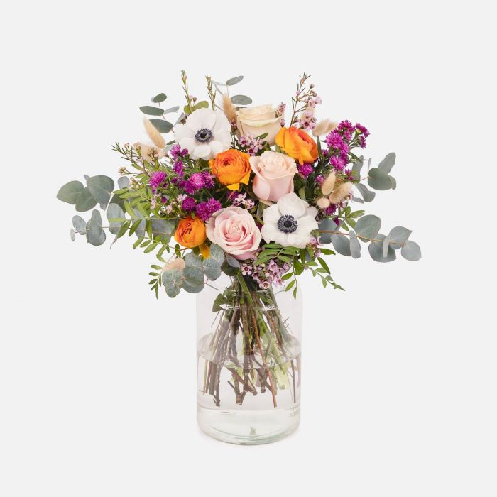 vase filled with water placed in front of white background flowers to give as gifts colorful flower bouquet inside