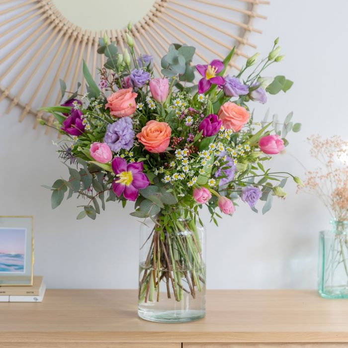 vase placed on wooden cabinet flowers to give as gifts flower bouquet in pink purple and green in it