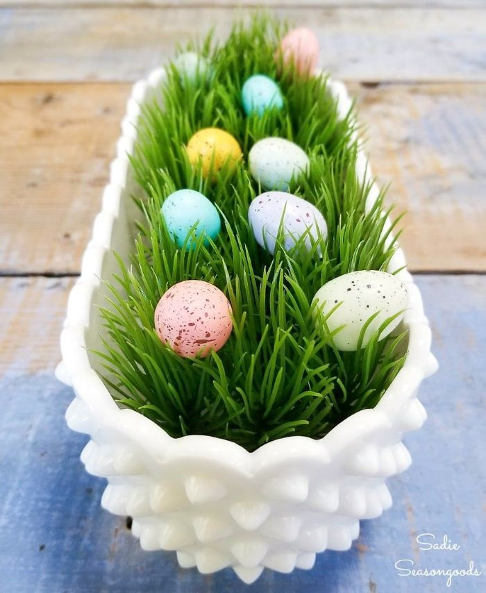 white ceramic pot filled with faux green grass diy easter decorations eggs inside in blue pink yellow purple