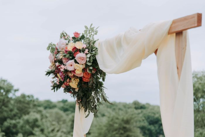 white curtain wrapped around wooden arch simple wedding decorations flower arrangement on the side