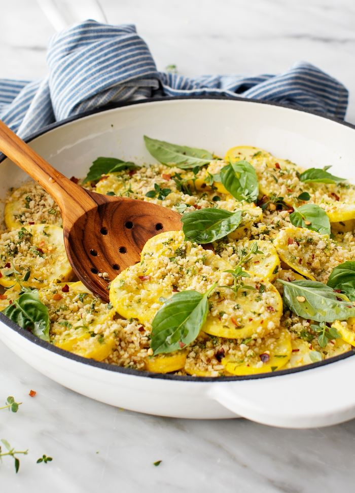 white saucepan filled with squash zucchini and yellow squash recipes garnished with cheese and basil leaves