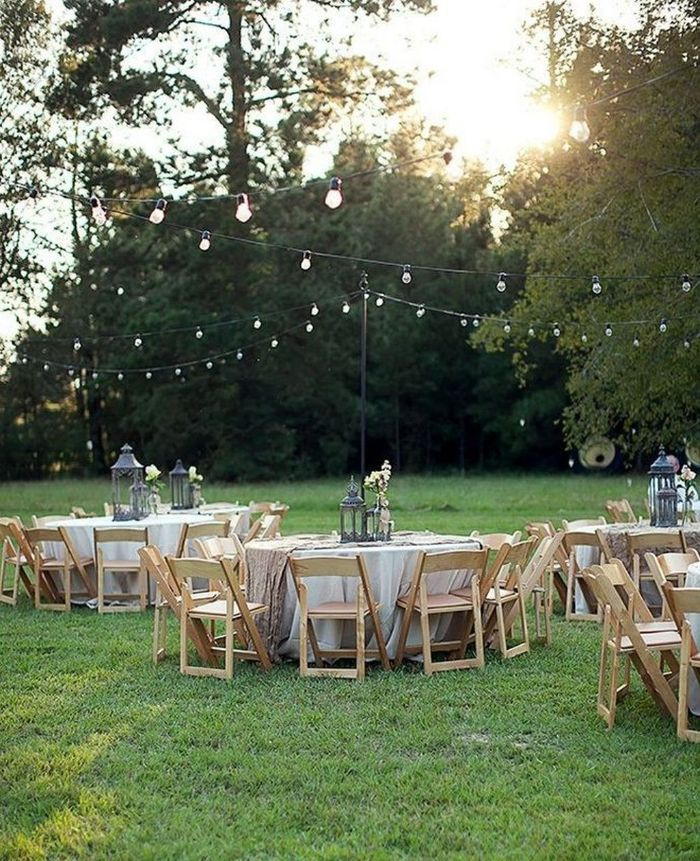 white table cloths on round tables arranged under strings of lights backyard wedding reception minimalistic decor