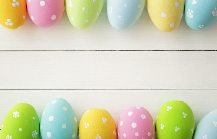 white wooden surface easter background eggs in different colors in the top and bottom edges of the photo