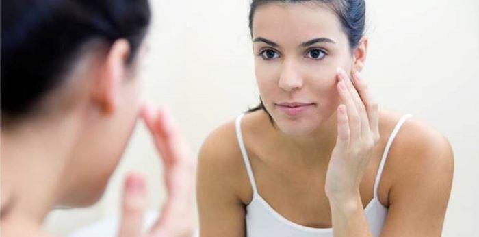 woman looking at herself in the mirror homemade face mask for acne with black hair wearing white top