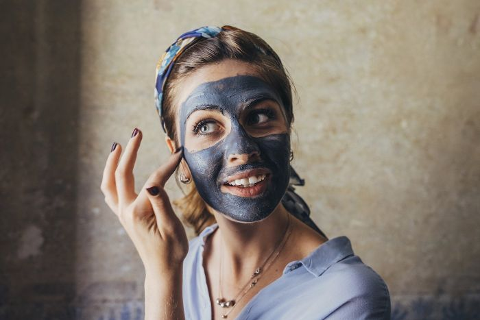 woman putting dark face mask on her face hydrating face mask wearing blue shirt