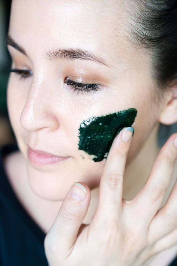 woman putting on face mask on her how to make a face mask for skin dark green color