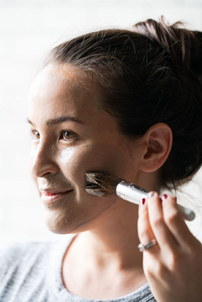 woman putting on mask on her face using a brush how to make a face mask for skin