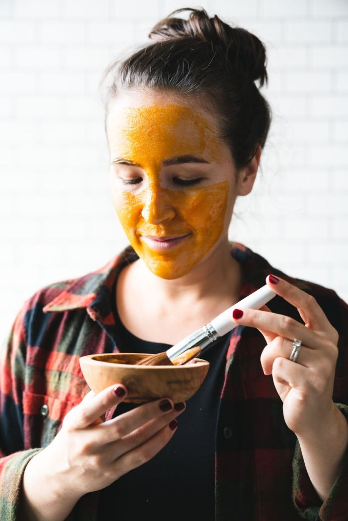 woman putting on yellow face mask how to make a face mask for skin wooden bowl and brush