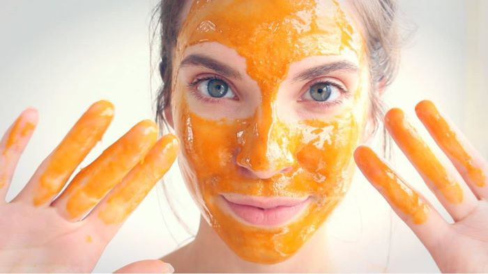 woman putting yellow face mask on her face skin care masks white background