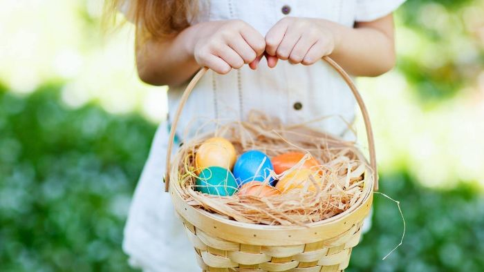 woman wearing white dress holding a basket adult easter basket filled with dyed easter eggs