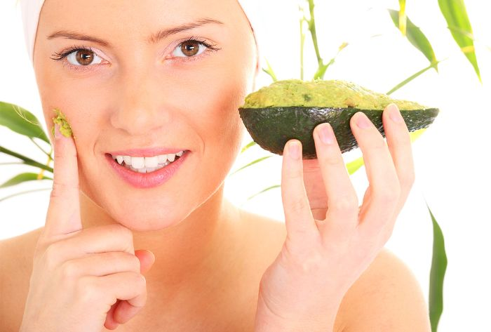 woman wearing white towel on her head diy face masks putting avocado mask on her face