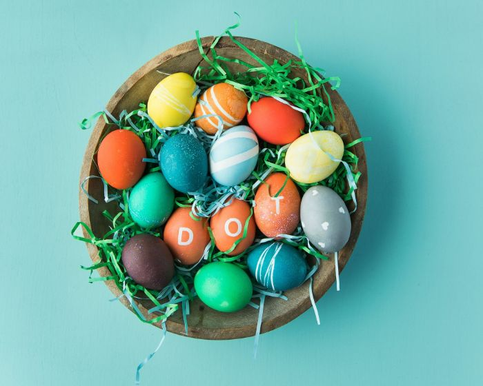 wooden bowl filled with eggs and green paper easter egg coloring decorated eggs